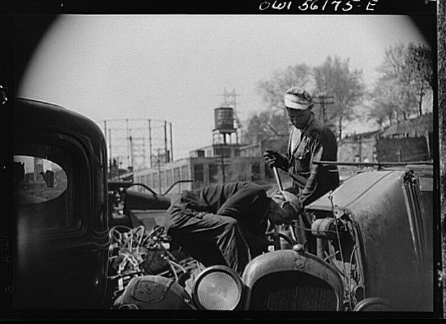 Two junkyard men taking a car apart