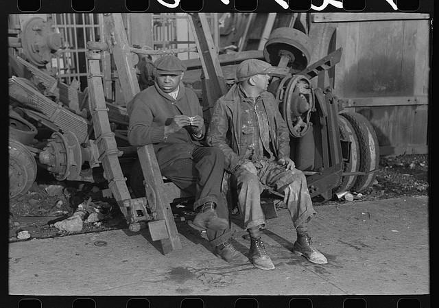 Men at junkyard on coffee break