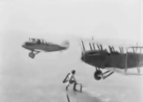 AMAZING HISTORICAL VIDEO: A WING WALKER FROM THE TWENTIES CHANGES THE WHEEL ON A PLANE IN MID-FLIGHT