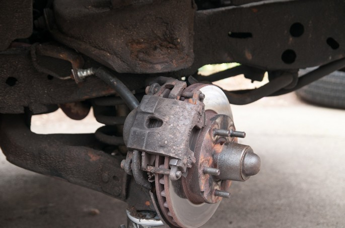 """So here we have it, the front suspension. Unequal length upper and lower control arms, coil springs, and single piston 10.5"""" brakes, all covered in a thick layer of undercoating. Somehow I was still optimistic at this point."""