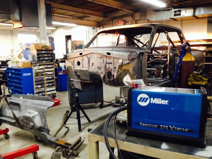 With 10 minutes off the clock and a stead hand, Kevin removed front of the car. He's going to be custom building a new front subframe and suspension system and that's going to have nothing to do with the factory stuff so, bombs away! The Miller plasma cutter made short work of that job.