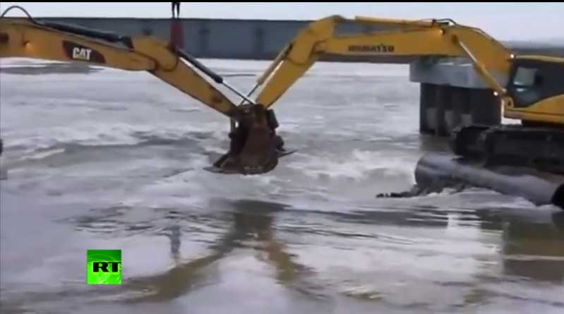 Watching Russian People Ferried Across A River In The Buckets Of Two Backhoes Is Pretty Awesome