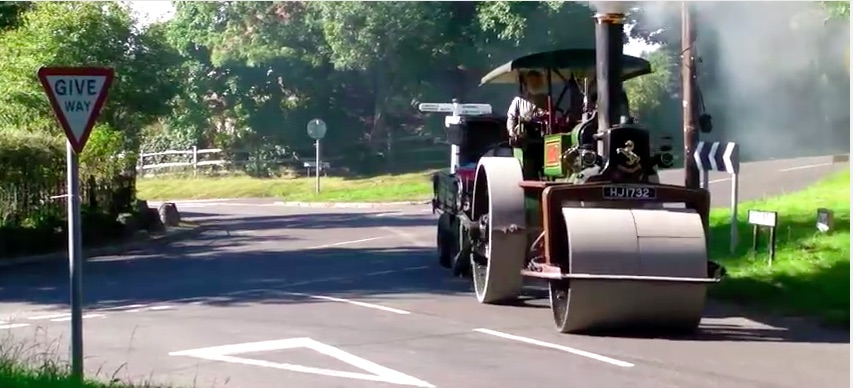 Watch This Massive Steam Powered Steam Roller Own The Road In England – The People In The Little Car Get A Surprise!